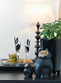 Ceramic cats and potted plant on black worksurface with glasses of sparkling wine in background