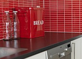 Empty milk bottles and red metal bread bin on kitchen worksurface with splashback of red mosaic tiles