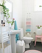 Pedestal sink between shelves of pink and pale blue towels in white-tiled bathroom with romantic atmosphere
