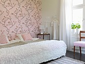 Twin beds pushed together with white blanket in romantic bedroom with pink, magnolia-patterned wallpaper