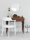 White armchair and antique bureau below round mirror and candelabra on floor