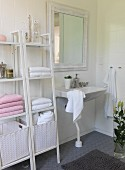 White shelves of towels and laundry baskets next to sink in romantic bathroom