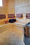 Modern sauna - colourful towels on backrest of wooden bench