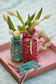 White tulips in bottles with hand-crocheted covers on pink tray with Easter greetings on tag