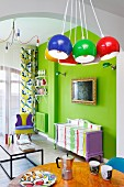 Colourful living area with neon-green wall, painted antique cabinet and brightly coloured, spherical lamps
