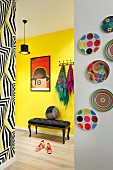 Framed red poster above antique, upholstered bench against yellow hallway wall, colourful plates on white wall and wall with patterned wallpaper