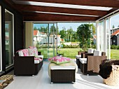 Conservatory with open sliding doors and rattan outdoor furniture