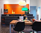 Black shell chairs around set table in front of kitchen island and orange fitted cupboards