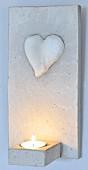 An Wand gehängtes Windlicht aus Beton mit appliziertem Herz und brennende Kerze