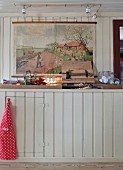 Colourful illustration above rustic, wood-clad kitchen counter