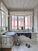 Grey sheepskin blankets on window seat in wood-clad conservatory with fabric roller blinds on lattice windows