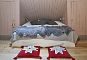 Comfortable bed with grey sheepskin blankets in niche in attic room; red cushions with abstract floral design on wooden floor