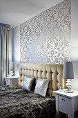 Elegant bedroom with button-tufted headboard, shiny silver-patterned wallpaper and plush blanket