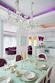 Elegantly set dining table in Neo-Baroque dining area with crystal chandeliers and purple accents