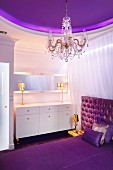 Elegant bedroom in shades of purple with gilt table lamps on white dressing table, purple ceiling panel and crystal chandelier