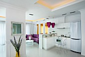 Glossy white floor in white, open-plan kitchen with purple and gold accents