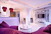 Offener eleganter weißer Wohnbereich mit violetten Farbakzenten, stimmungsvoller indirekter Beleuchtung und Pendelleuchten über Küchentheke