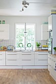 Spacious, modern kitchen with bar handles on white drawer fronts
