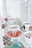 Collectors' cups and saucers with retro, graphical patterns on glass shelves in display case