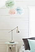Retro-style bedside table and pastel fabric flowers against white-painted wooden wall