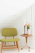Retro upholstered chair and candles and flowers on side table in white, wood-clad attic room
