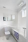 Weisses Designerbad, Toilette mit Spülkasten an gefliester Wand, neben Badewanne mit Marmorbelag an Frontseite und auf Boden