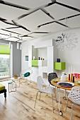 Stühle mit Lochmuster an rundem, rollbarem Tisch in luftigem Wohnraum