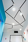 Pendant lamp hanging from hallway ceiling with geometric pattern