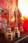 Electric candlesticks with religious motifs, tiny Buddha statues and Indian artwork on shelf
