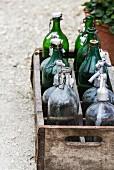 Holzkiste mit leeren Flaschen auf einem Gartenweg