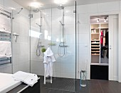 Floor-level double shower with glass screen in minimalist bathroom with sliding door leading to dressing room