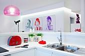 Blick über weisse Küchentheke auf Portraitfotografien an weißer Wand und rosafarbene Pendelleuchte