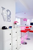 Lettering spelling 'LOVE' above sideboard and red bar stools at white kitchen counter in open-plan interior