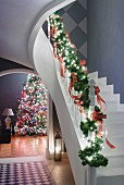 Staircase balustrade decorated with fir branches and view of decorated Christmas tree through arched doorway to one side