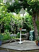 Vintage Bistrotisch und Klappstuhl auf Holzdeck in sommerlichem Garten