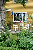 White garden furniture on terrace adjoining yellow-painted wooden house