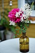 Sommerblumen in Apothekerflasche auf Gartentisch