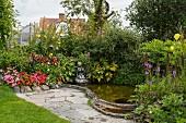 Blühende Blumen um kleinen Teich, Steinfigur am Wasserrand, davor Plätzchen aus Natursteinbelag
