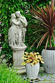 Potted plants around romantic statue of couple on plinth in garden