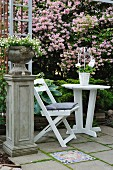 Planted urn on plinth next to white garden chair and table on terrace