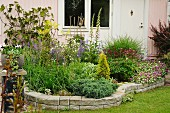 Flowering herbaceous border with stone surround against house façade