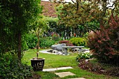 Summery garden with small potted tree, stone bench and boulders beside round garden pond