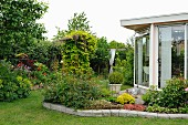 Summery garden with herbaceous border in front of conservatory extension