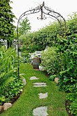 Metal trellis arch over grass path with stepping stones in garden