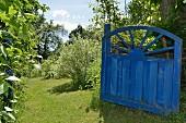 Open, blue, vintage wooden gate in summery garden