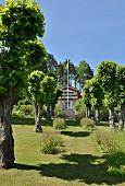 Sommerlicher Garten mit Allee zum Landhaus mit schwedischer Fahne und Treppenaufgang