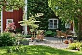 Blick vom Garten auf möblierten Vorplatz mit Kiesboden, rotbraun gestrichenes Holzhaus, in Sommerstimmung