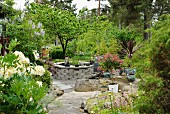 Pond in stone surround and Chinese pots on gravel area in landscaped garden