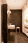 Designer bathroom with grey tiles on walls and floor, minimalist fittings and custom shelving below window in niche