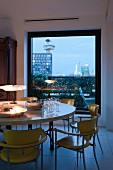 Romantically lit dining table with retro chairs in front of floor-to-ceiling window with view of city at twilight
